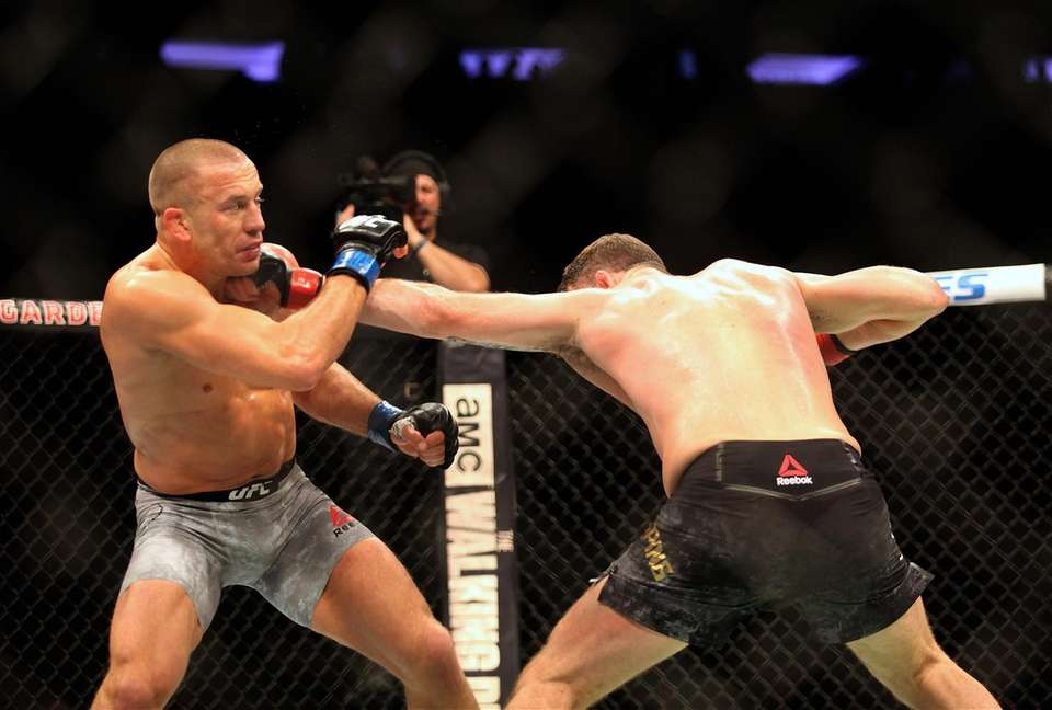 Michael Bisping, right, and Georges St-Pierre exchange strikes