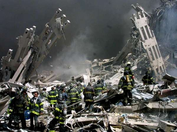 Firefighters make their way through rubble after terrorists
