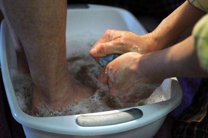 Emma Decker has her feet washed by her