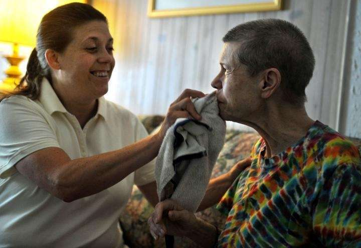Lynn Decker cleans up her mom after a
