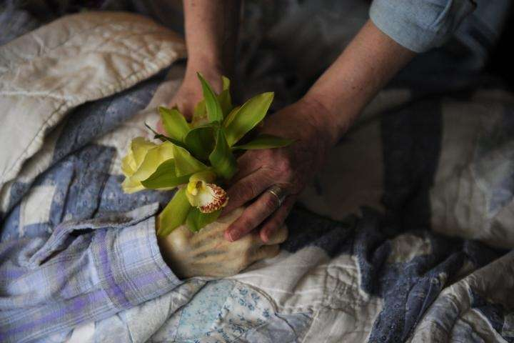 Lynn Decker places flowers in the lifeless hands