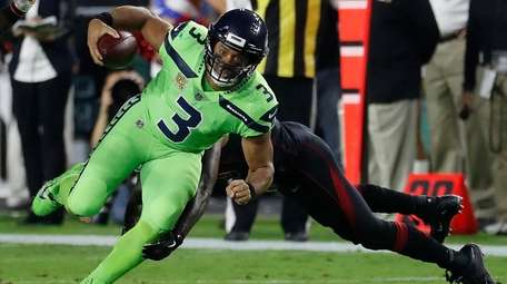 Seahawks quarterback Russell Wilson eludes the tackle during a