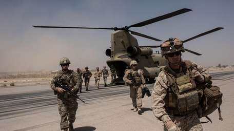 U.S. service members walk off a helicopter on