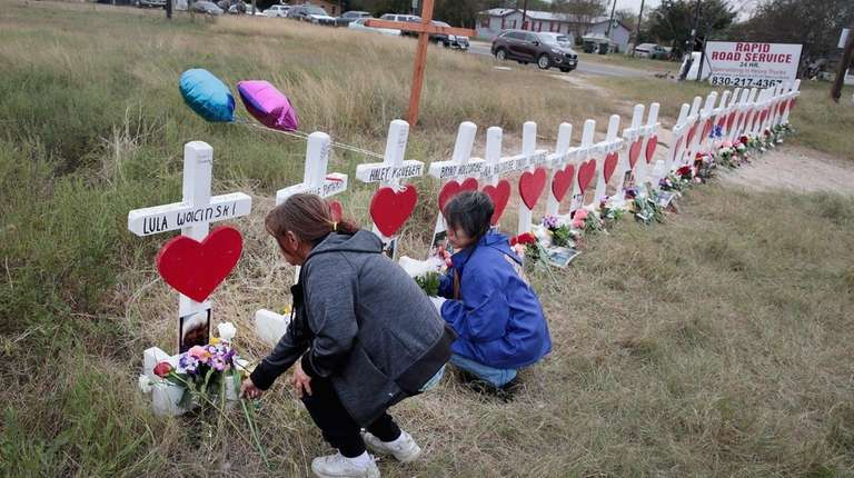 Visitors leave flowers at a memorial where 26