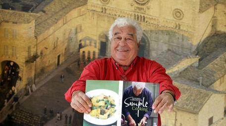 Italian chef Antonio Carluccio holds a copy of