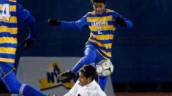 Pierson/Bridgehampton's Jose Cruz, bottom, slide tackles Lansing's Langston