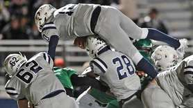 Oceanside quarterback Tommy Heuer #10 leaps over a