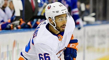 The Islanders' Josh Ho-Sang controls the puck against
