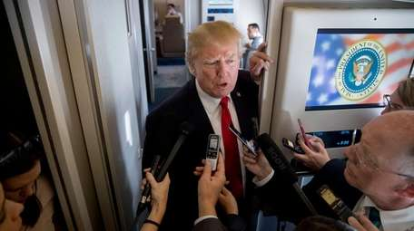 President Donald Trump speaks to reporters aboard Air