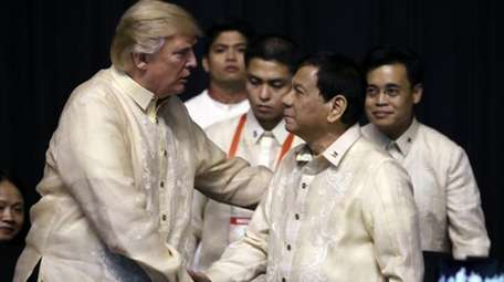 President Donald Trump, left, shakes hands with Philippines