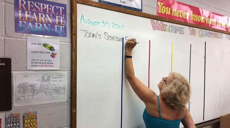 A computer science teacher prepares her classroom for