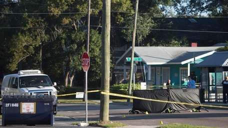 Law enforcement agents investigate a fatal shooting in