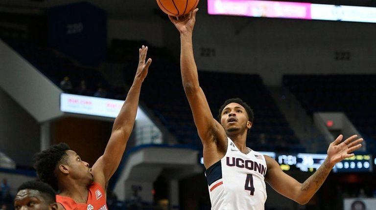 Connecticut's Jalen Adamsmakes a basket over Stony Brook's