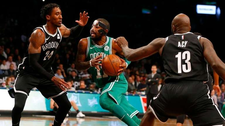 Kyrie Irving of the Celtics drives between Nets'