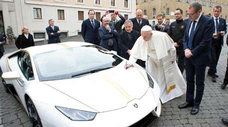 Pope Francis writes on the bonnet of a