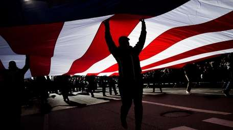 People carry an American flag as they march