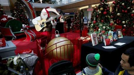 Santa sings to passersby at the Roosevelt Field