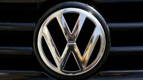 The Volkswagen logo is photographed on a car