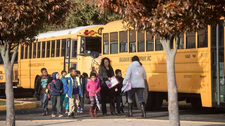 Children boarding school buses at Freeport's New Visions