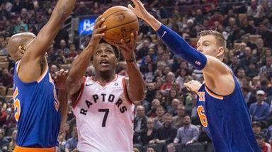 Raptors guard Kyle Lowry drives between Knicks forward