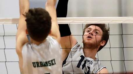 Eastport-South Manor's Tom Ogeka spikes the ball for