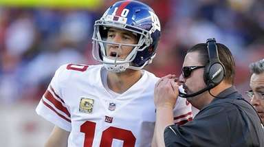 Giants quarterback Eli Manning talks with head coach Ben