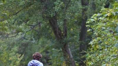 A mother and child take a walk outdoors.