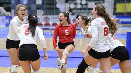 The Connetquot girls volleyball team celebrates after a