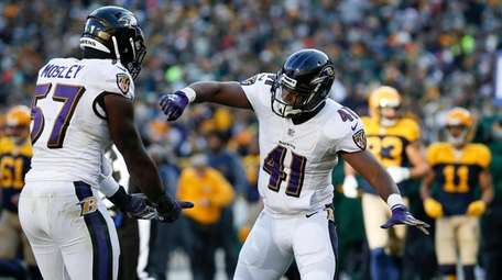 Baltimore Ravens' C.J. Mosley and Anthony Levine react