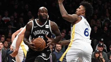 Nets forward Quincy Acy drives, defended by  Warriors