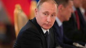 Russian President Vladimir Putin listens to his Uzbek