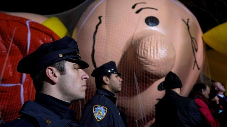 NYPD officers stand near Macy's parade balloons after