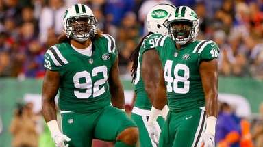 Leonard Williams and Jordan Jenkinsof the Jets reacts