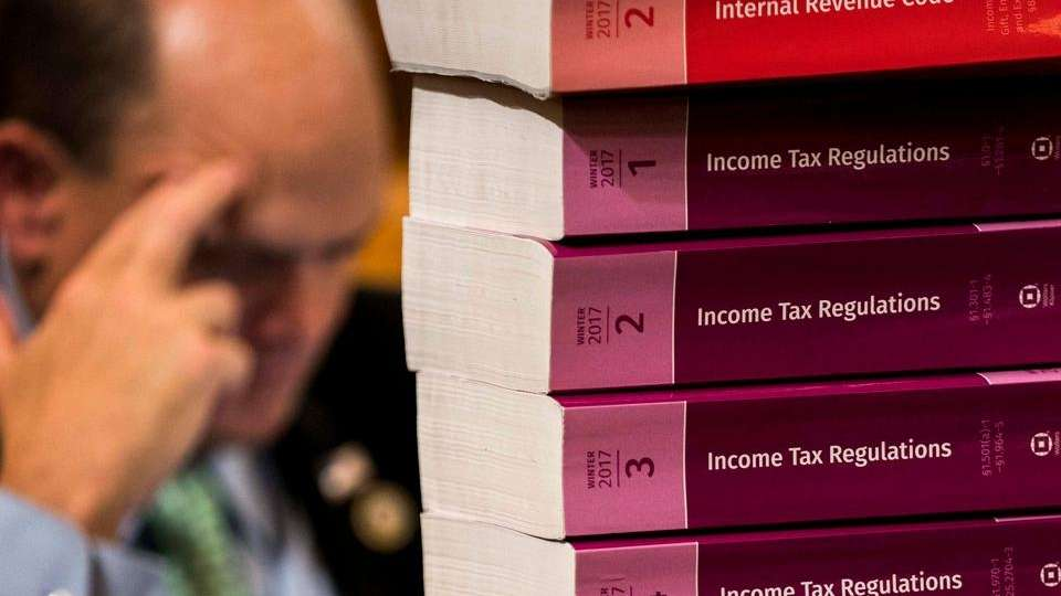 Tax code books are stacked on the dais