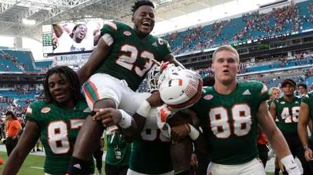 Miami tight end Christopher Herndon IV is carried