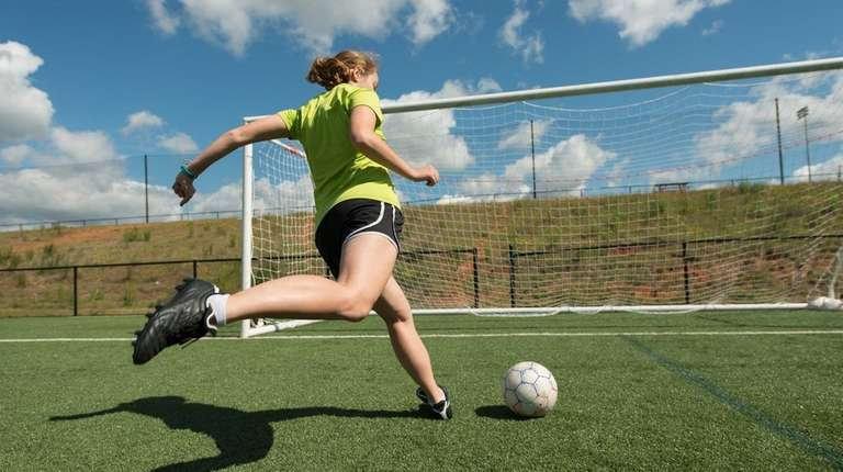A soccer player practices shots on a turf
