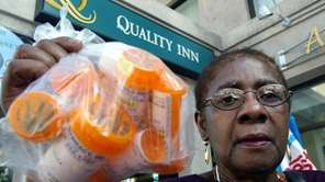 A woman shows a bag containing the 13