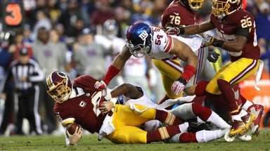 Kirk Cousins of the Redskins is sacked by Olivier