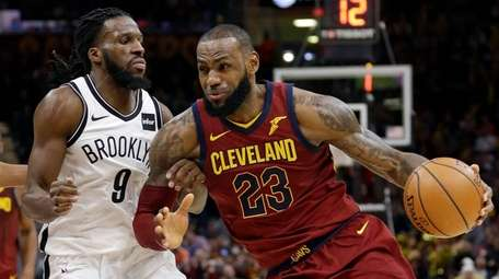 The Cavaliers' LeBron James drives against the Nets'