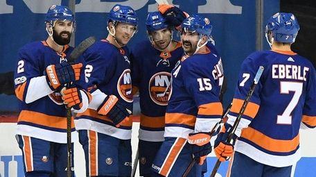 Islanders players celebrate the game-winning goal by Josh