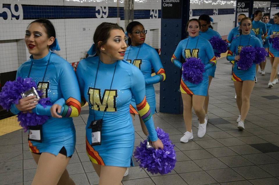 Cheerleaders wait for the subway at Columbus Circle