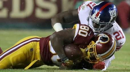 Giants safety Landon Collins, right, takes down Redskins