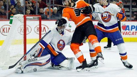 New York Islanders goalie Thomas Greiss, left, blocks