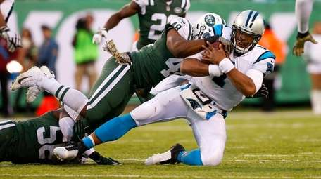 Cam Newtonof the Panthers is tackled in the
