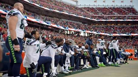 Seahawks players sit and kneel during the playing