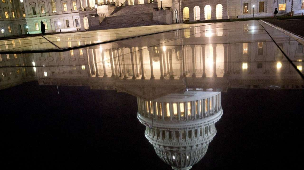 The U.S. Capitol dome is reflected before sunrise