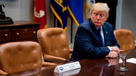 President Donald Trump looks at an empty chair