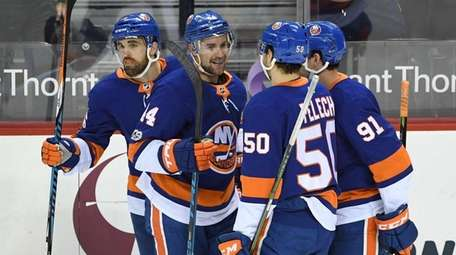Islanders players celebrate a goal by left wing