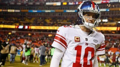 Giants quarterback Eli Manningwalks off the field after