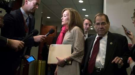 Reporters pose questions to Rep. Kathleen Rice, center,
